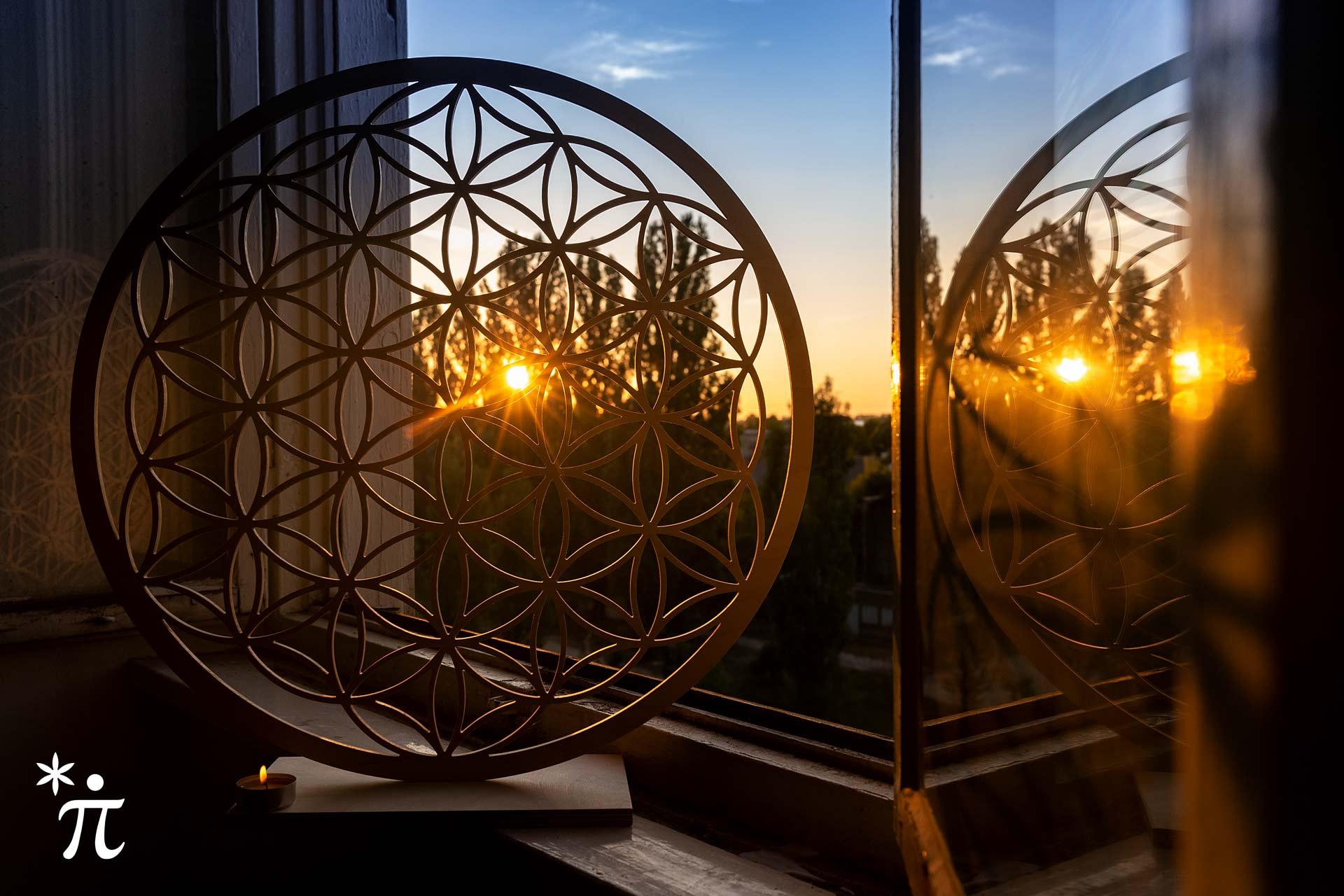 Blume-des-Lebens-aus-Holz-mit-Fuss-am-Fenster-bei-Sonnenuntergang