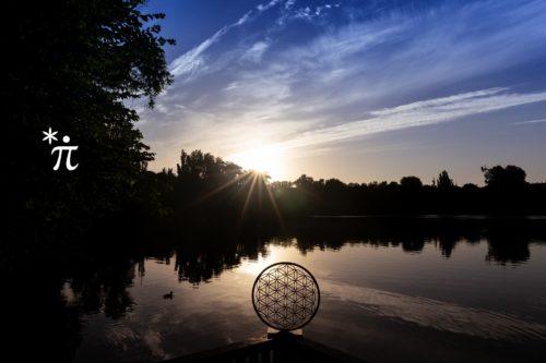 Blume-des-Lebens-aus-Holz-mit-Fuss-Sonnenaufgang-am-See