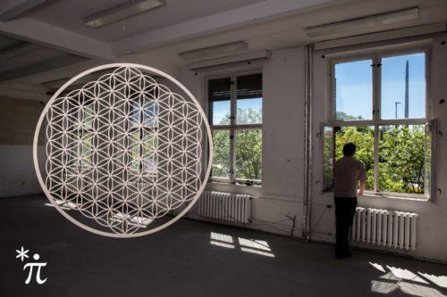 Erweiterte-Blume-des-Lebens-aus-Holz-mit-Mann-am-Fenster